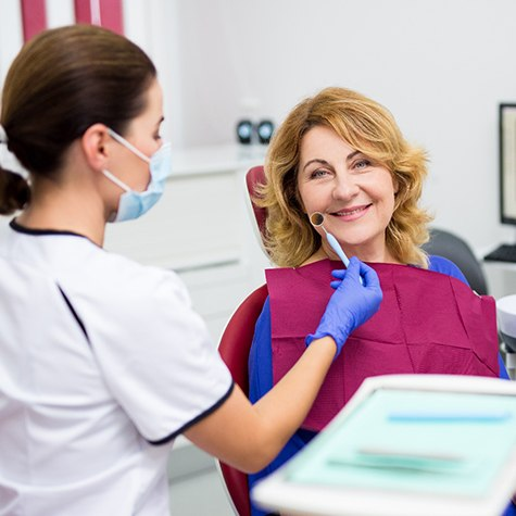 An older woman smiling while a dentist examining her smile for a dental implant procedure in Doylestown