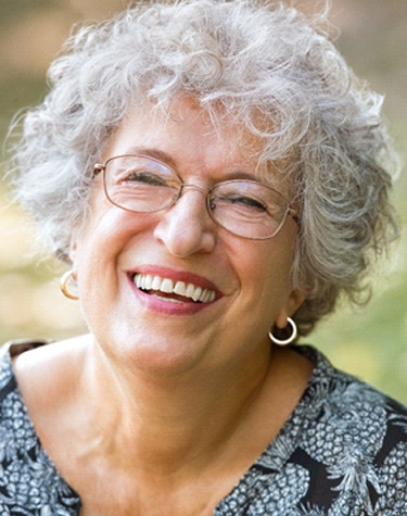 An older woman wearing glasses and smiling, showing off her new dental implants