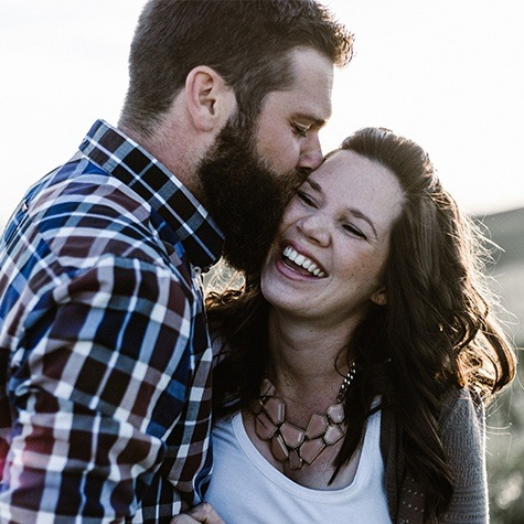 Woman laughing after smile makeover man kissing her cheek