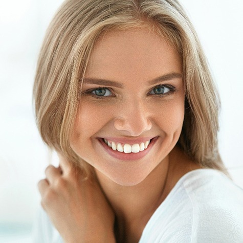 A young woman with blonde hair smiling to show off her new and improved smile