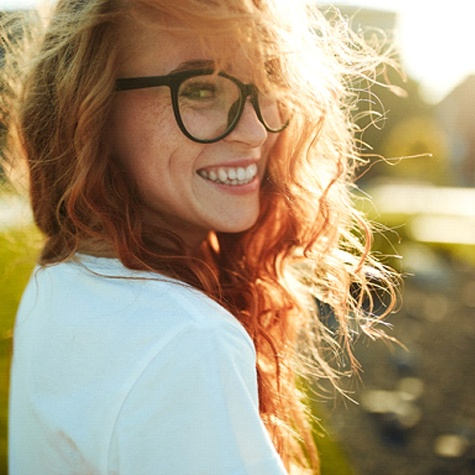 Red haired woman with glasses smiling with dental crowns in Doylestown, PA