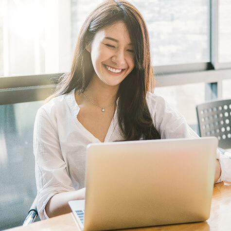 person smiling and working on a laptop