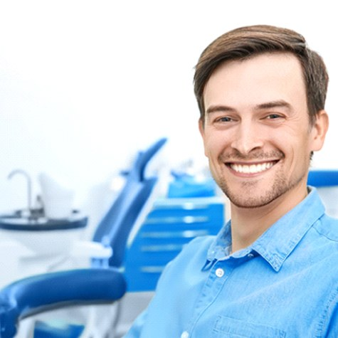 A young man sitting in a dentist's chair waiting to see the dentist who will examine his smile for implant placement