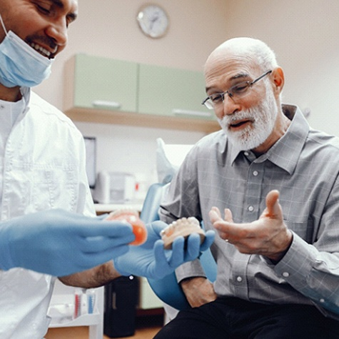 A dentist talking with an older gentleman about the benefits of implant-retained dentures
