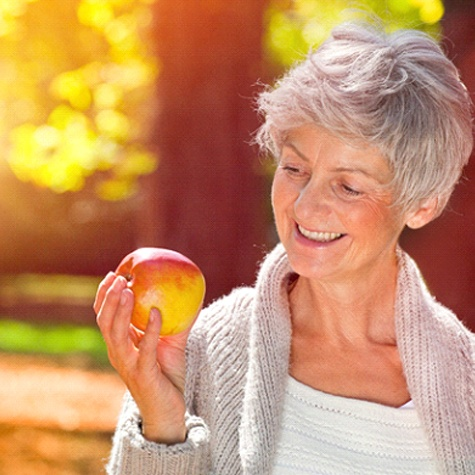An older woman wearing a cardigan outside and holding an apple, smiling after receiving her new implant-retained dentures
